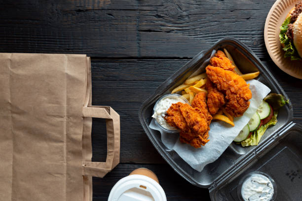 hamburger, french fries and fried chicken in takeaway containers on the wooden background. food delivery and fast food concept - food delivery imagens e fotografias de stock