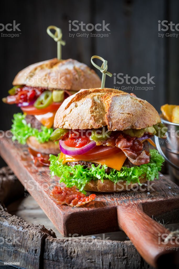 Hamburger made of bacon, tomato and beef on wooden plank stock photo
