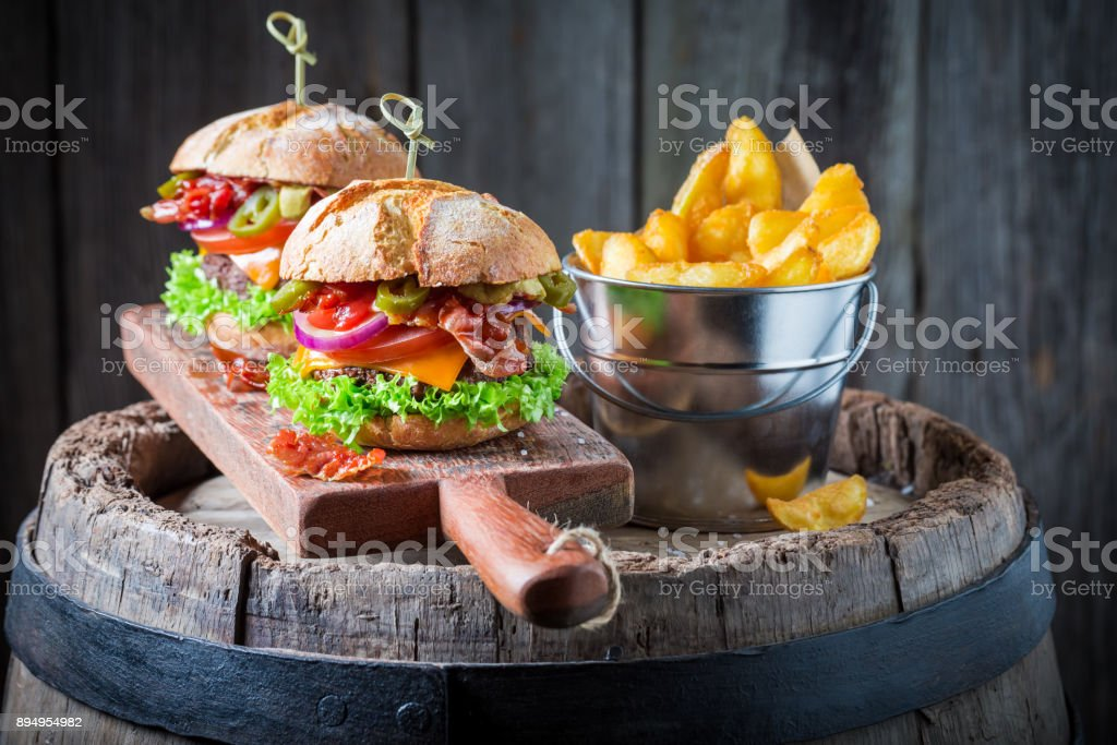 Hamburger made of beef, vegetables and cheese with chips stock photo