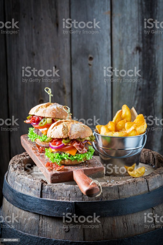 Hamburger made of lettuce, beef and cheese on wooden board stock photo