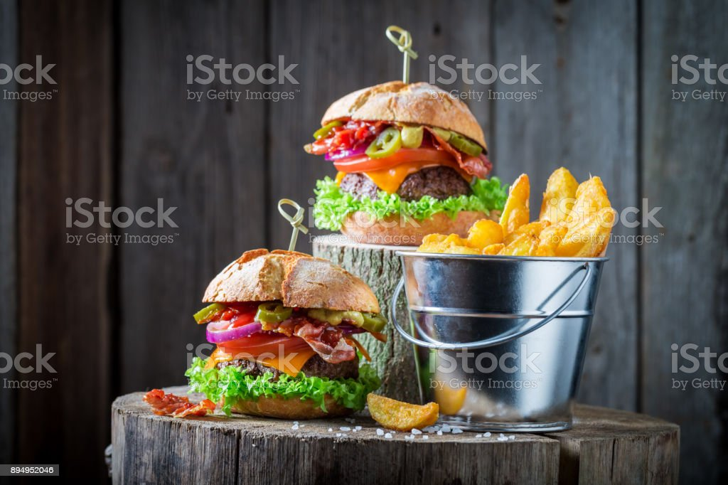 Hamburger made of lettuce, beef and cheese served with chips stock photo
