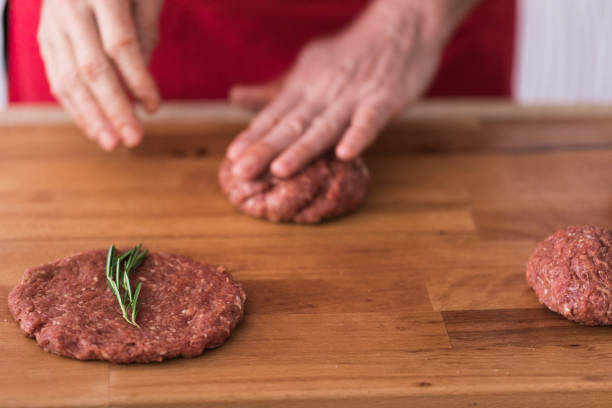 Hamburger making process, hand shaping minced steak, close-up, selective focus stock photo