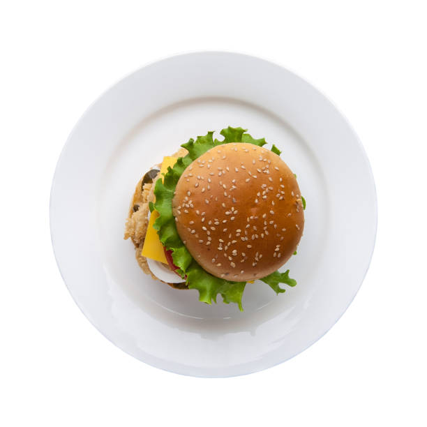 hamburger on a white plate hamburger with lettuce in a plate on a white background, top view high section stock pictures, royalty-free photos & images