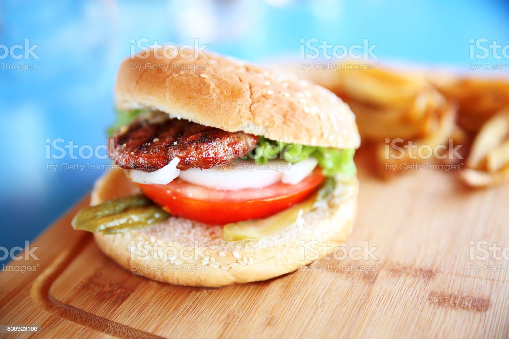 Hamburger on sesame seed bun with fixings stock photo