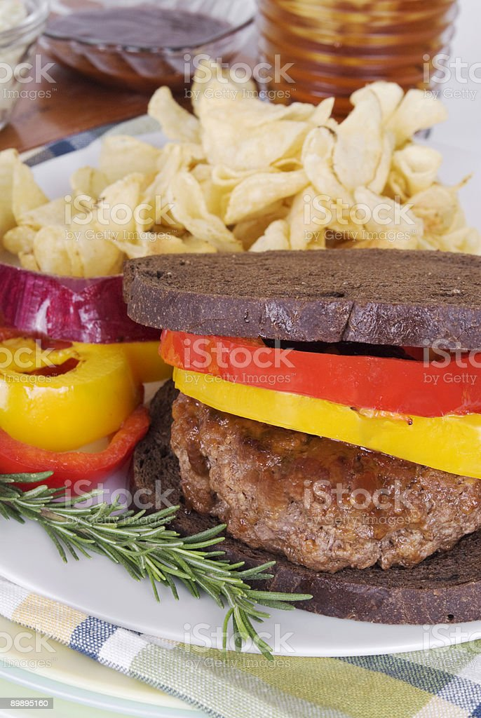 hamburger on toasted pumpernickel bread with yellow and red peppers royalty-free stock photo