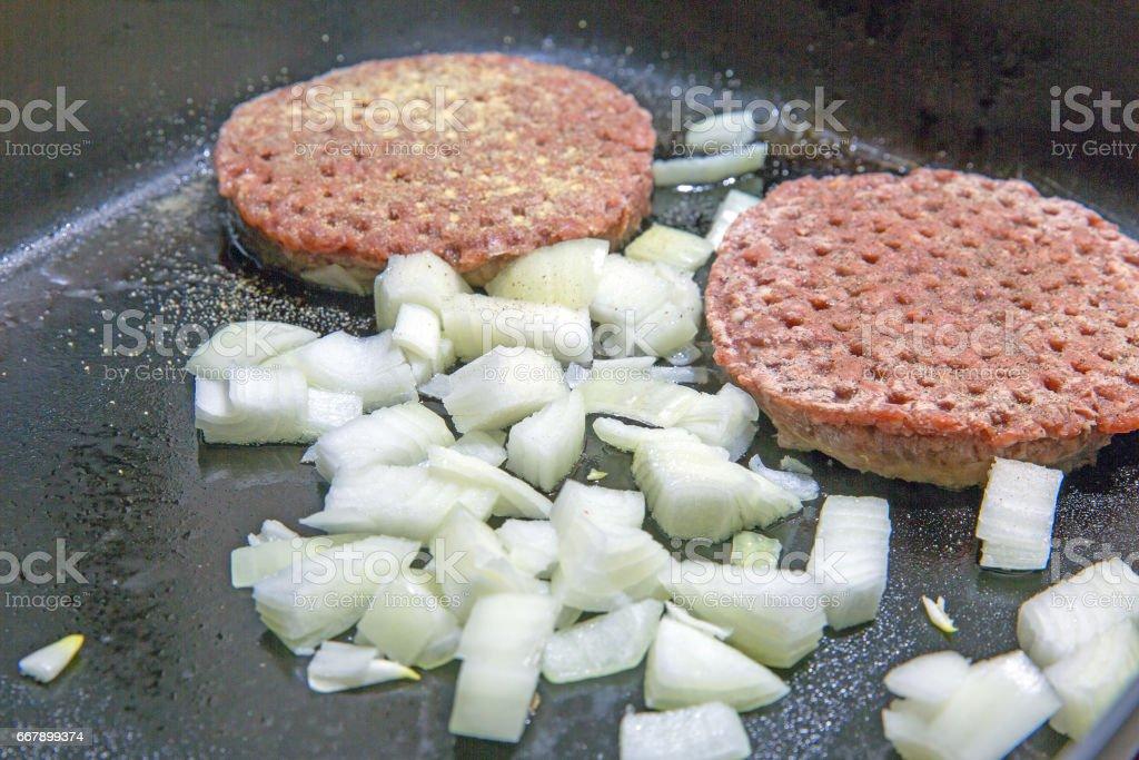 hamburger patties cooking on greasy fry pan closeup stock photo