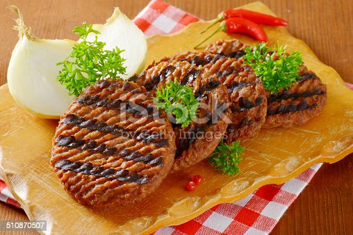 grilled hamburger patties with garnish on wooden cutting board and chequered dishtowel
