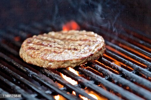 Hamburger patty on hot barbecue grill with flames