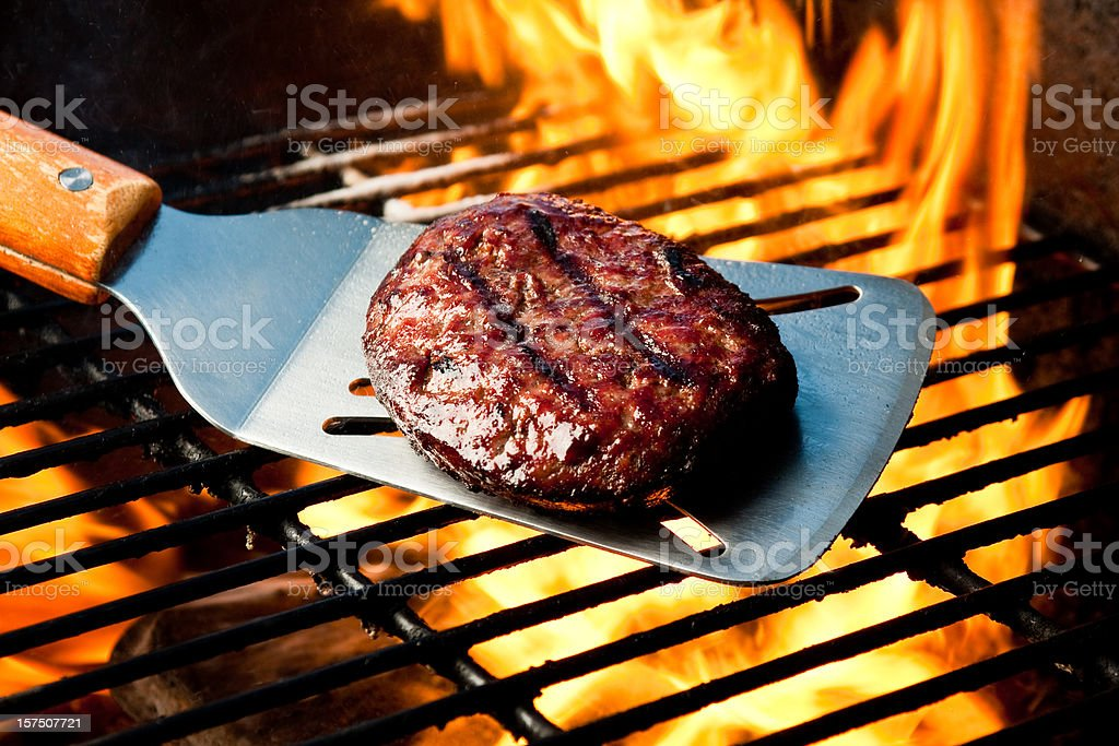 Hamburger Patty on Grill with Fire stock photo