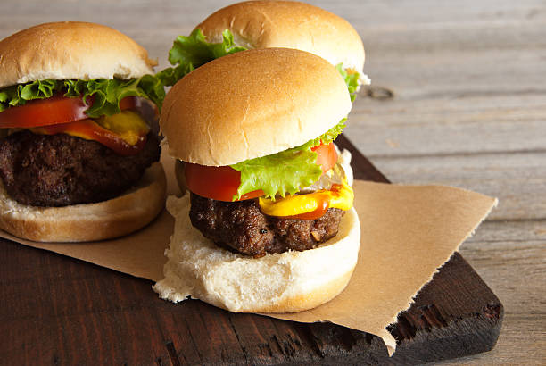 Hamburger Sliders on Left Three hamburger sliders with lettuce, tomatoes, pickles, mustard and ketchup on a rustic cutting board and table. slider burger stock pictures, royalty-free photos & images
