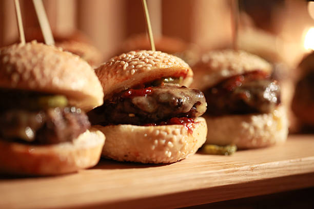 Hamburger sliders Hamburger slider on a rustic cutting wooden board with melted cheese slider burger stock pictures, royalty-free photos & images
