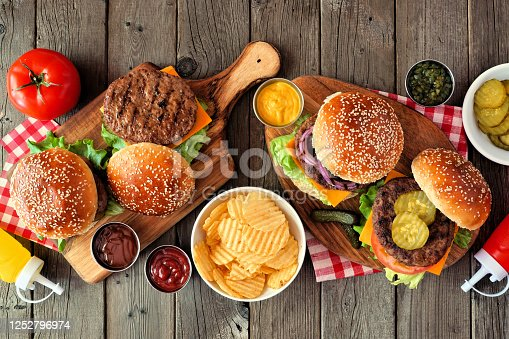 BBQ hamburger table scene. Top view over a dark wood background.