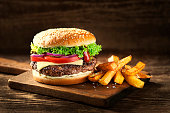 Delicious Hamburger with cheese and french fries on wooden table and dark background