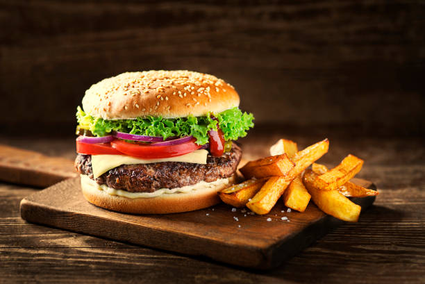 Hamburger with cheese and french fries stock photo