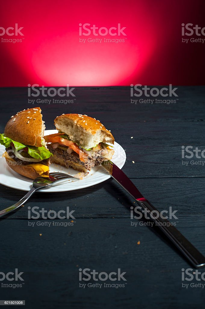Hamburger with fork and knife on wooden table Lizenzfreies stock-foto