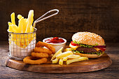 istock hamburger with french fries and onion rings 865789194