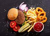 istock hamburger with french fries and onion rings, top view 865789998