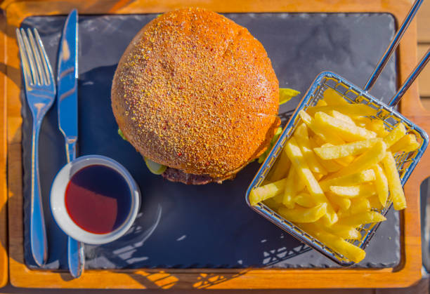 Hamburger with French Fries on a Stone Plate with Eating Utensil stock photo