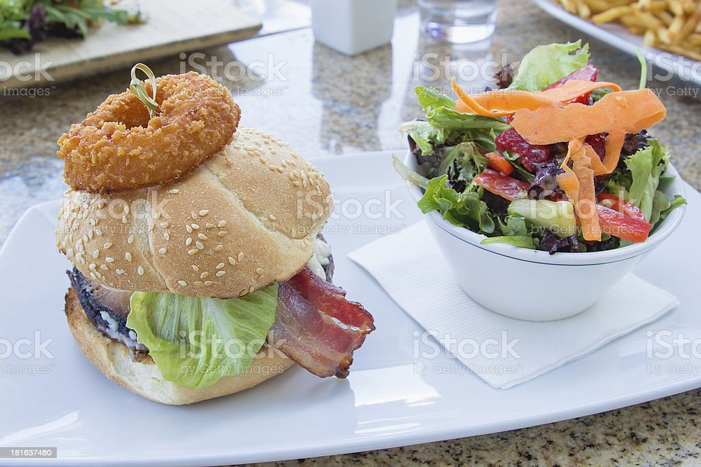 Hamburger with Onion Ring and Colorful Salad royalty-free stock photo