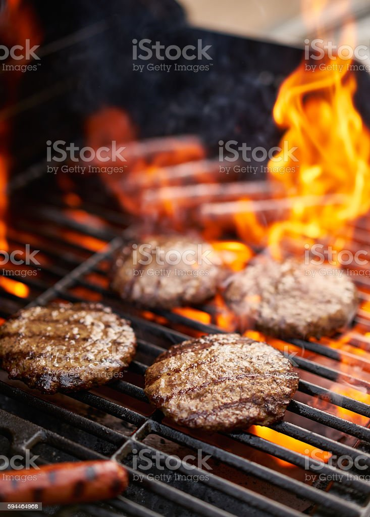 hamburgers and hot dogs being grilled stock photo