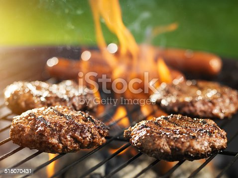 istock hamburgers and hotdogs cooking on flaming grill 515070431