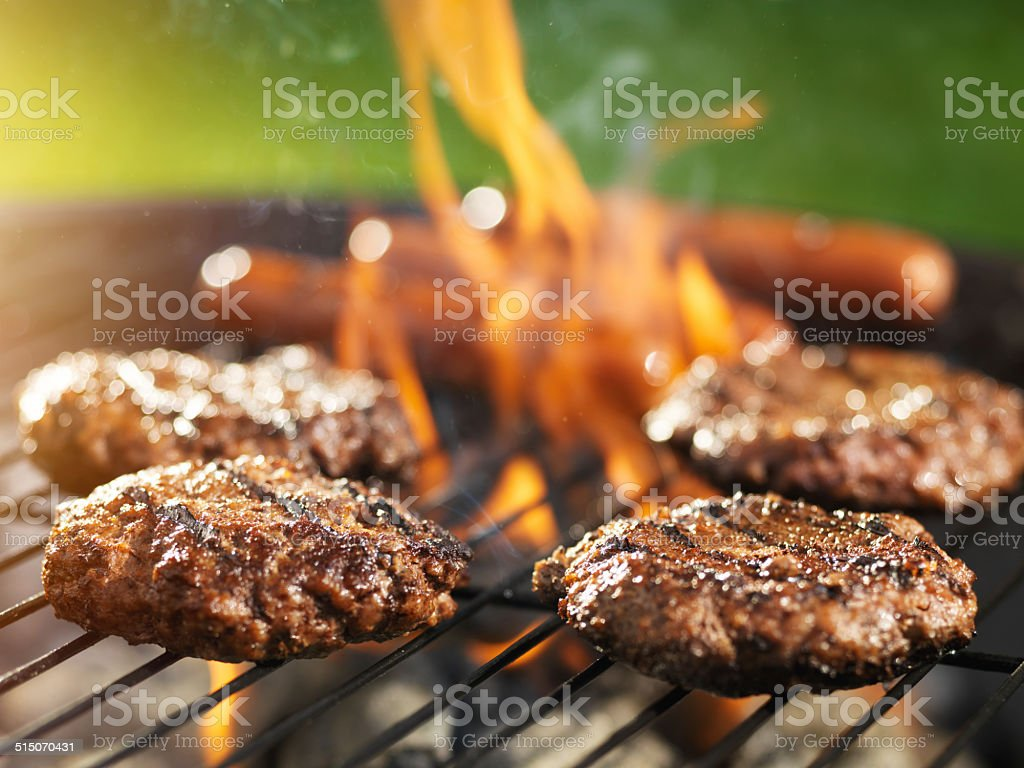 hamburgers and hotdogs cooking on flaming grill stock photo