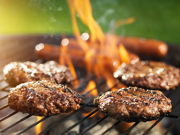 hamburgers and hotdogs cooking on flaming grill - barbecue grill stock photos and pictures