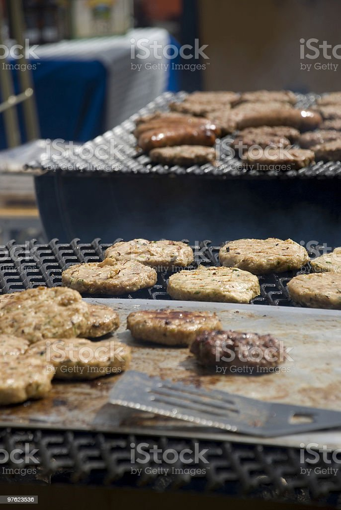 Hamburgers cooking on barbeque royaltyfri bildbanksbilder