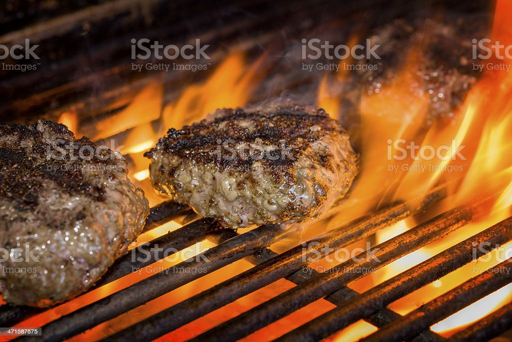 Hamburgers on a Flaming Grill stock photo