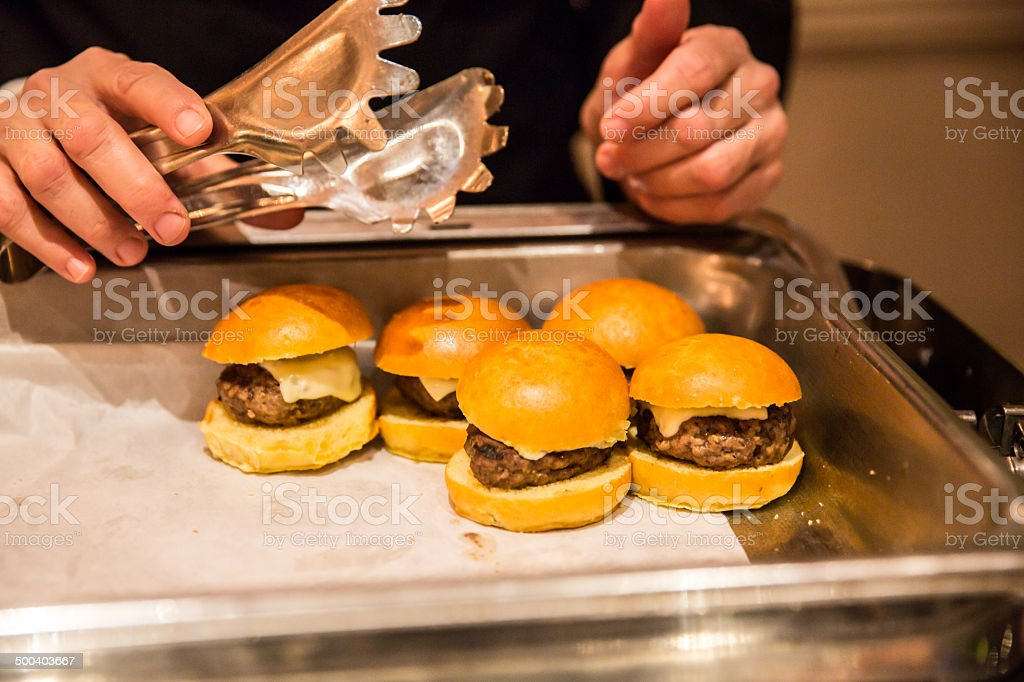Hamburgers on rolls being served at party buffet royalty-free stock photo