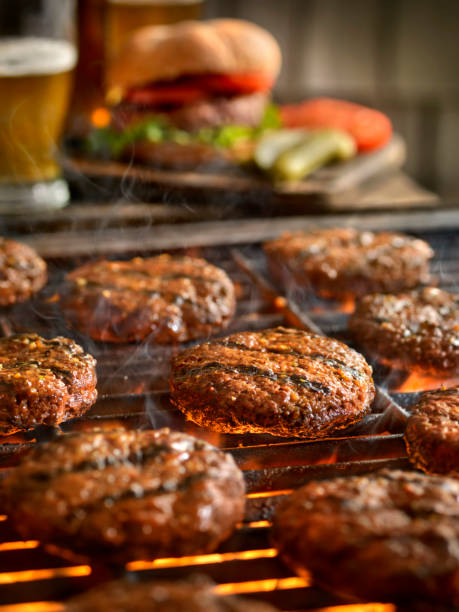 Hamburgers on the BBQ with Beers stock photo