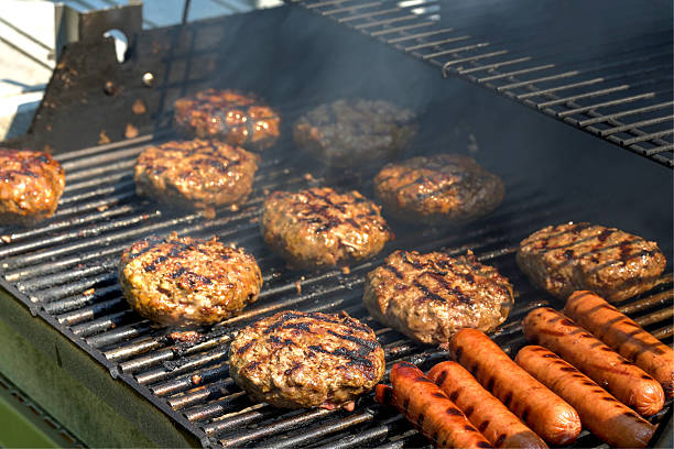 hamburgers on the grill - barbecue grill stock photos and pictures