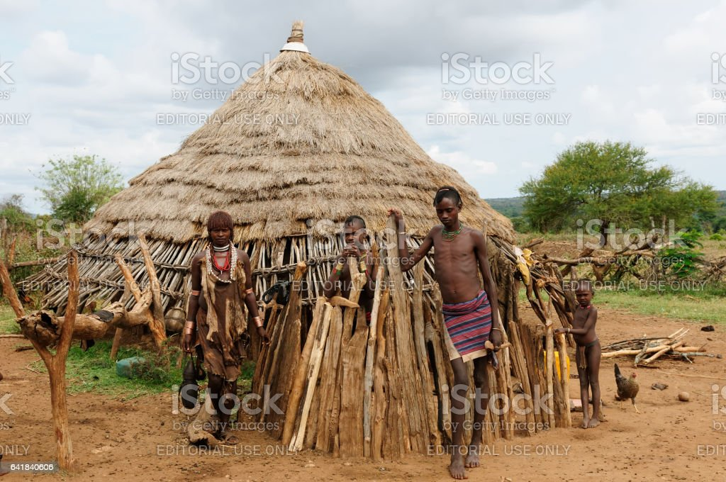 Hamer family standing in front of its traditional house stock photo