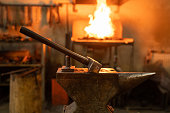 istock Hammer and anvil in forge on blurred background 1223869809