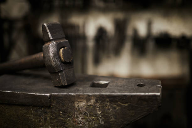Hammer and anvil in smithery Close-up of heavy hammer placed on durable steel anvil in dark smithery anvil stock pictures, royalty-free photos & images