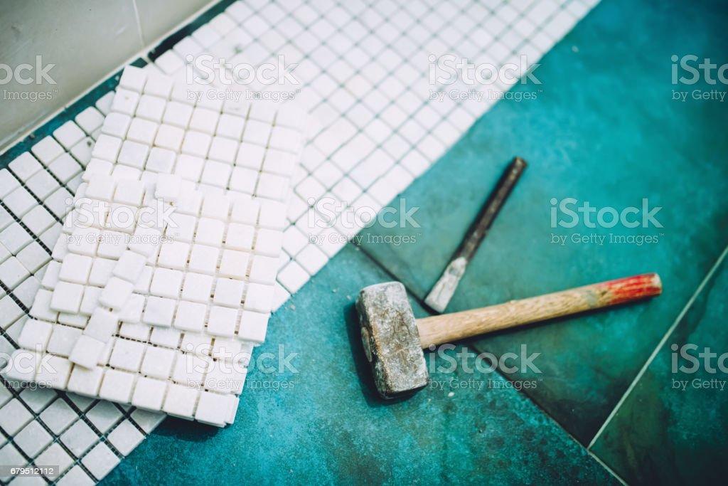 Hammer and mosaic, white marble stone ceramic tiles stock photo
