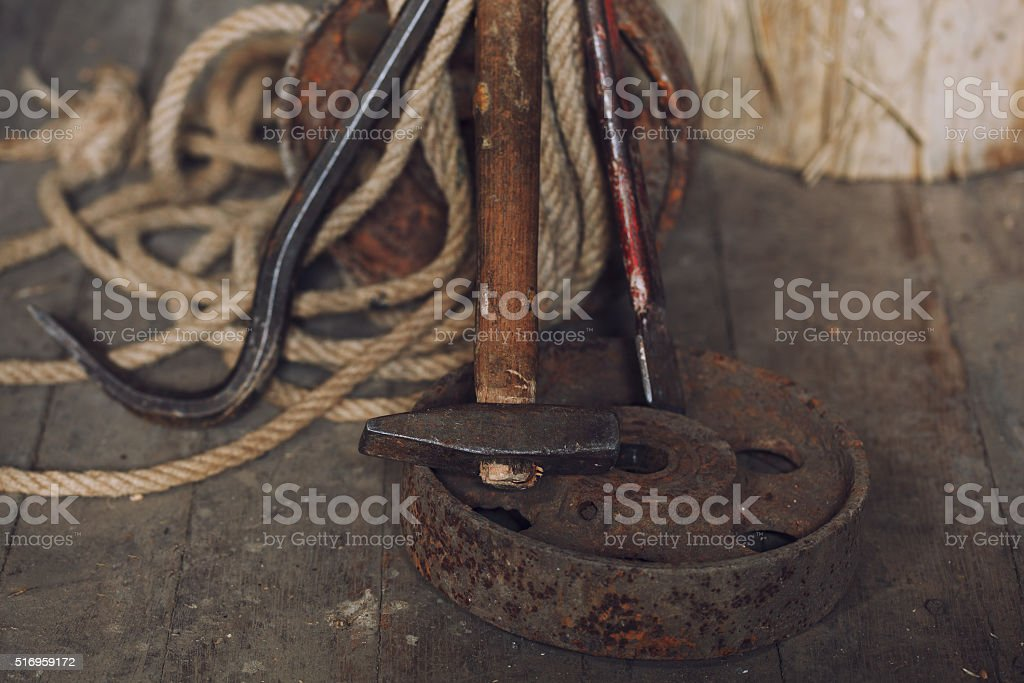 hammer and nail puller lays on wooden floor stock photo