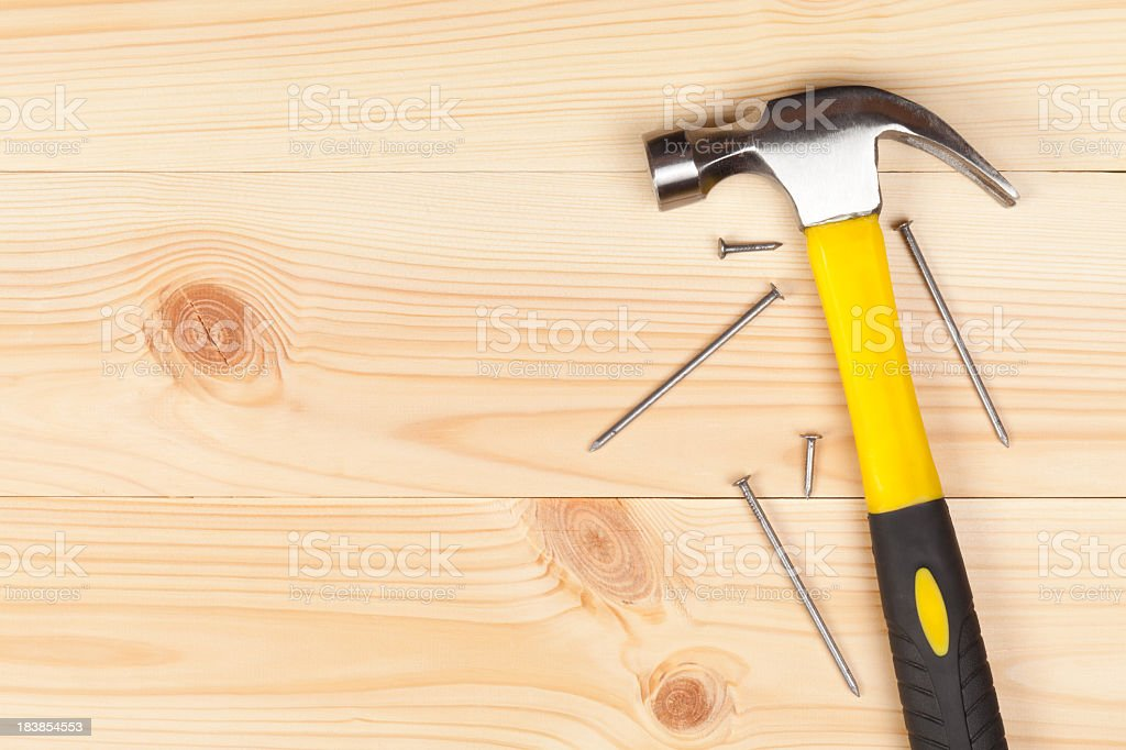 Hammer and nails on a wooden table stock photo