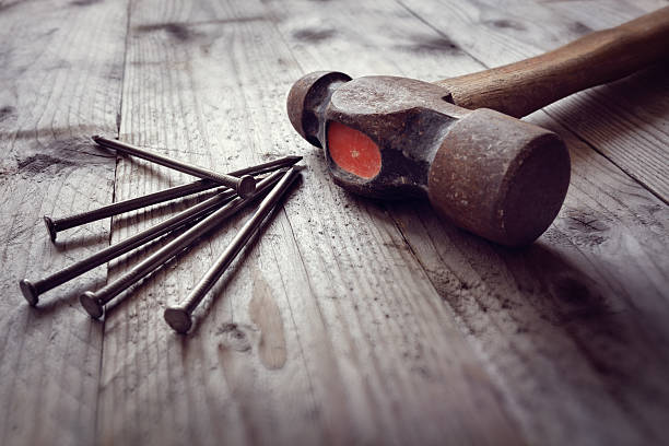 Hammer and nails Hammer and nails on floorboards concept for construction, diy, tools and home improvement nail work tool stock pictures, royalty-free photos & images
