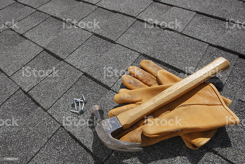 Hammer and pair of gloves and nails on rooftop stock photo