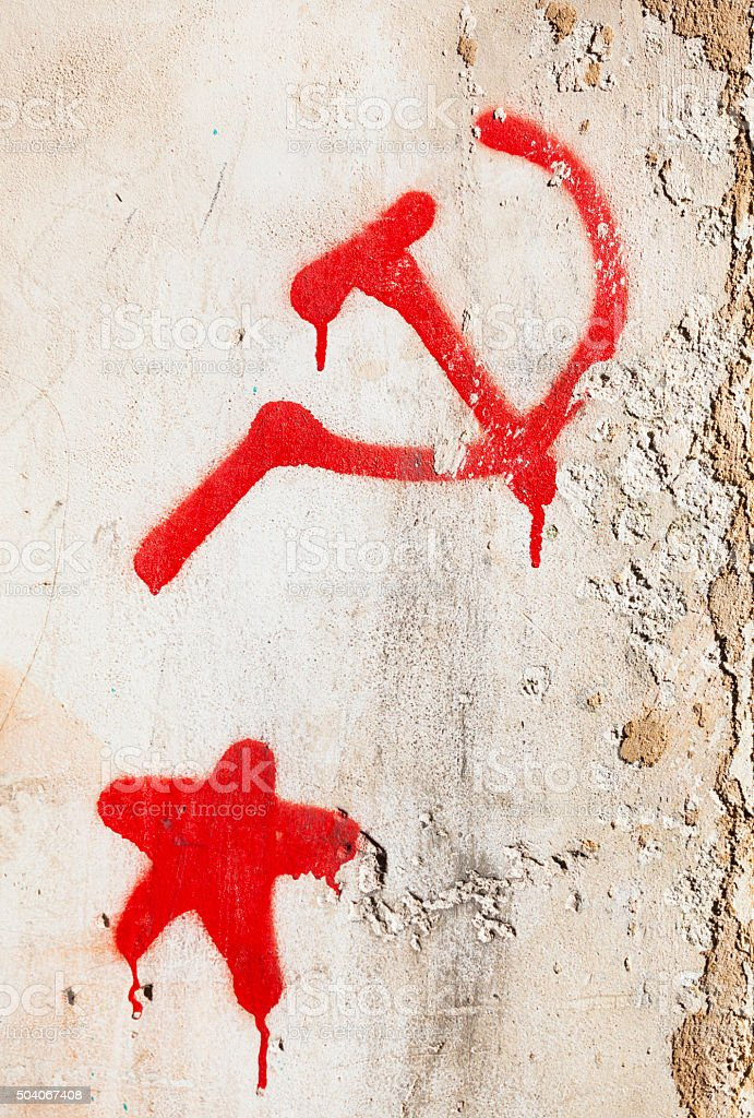 Hammer and sickle next to a red star on wall. stock photo