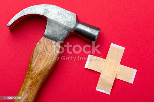 istock Hammer and strips on white background. Foreground. Risk concept home DIY and work without protection and security. 1049920066