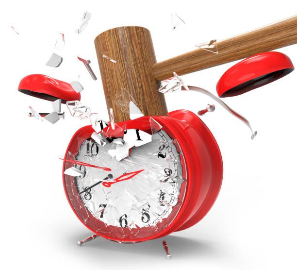 Hammer hitting an alarm clock stock photo
