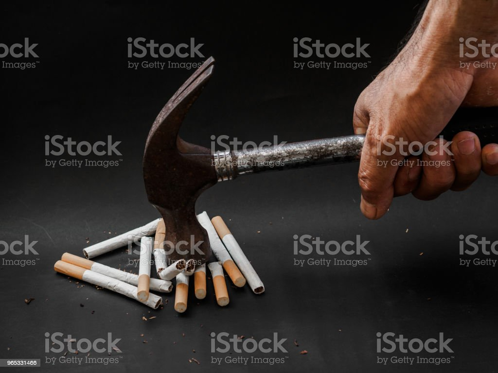 Hammer hitting and destroy cigarettes on black background. Quitting smoking concept. world no tobacco day royalty-free stock photo