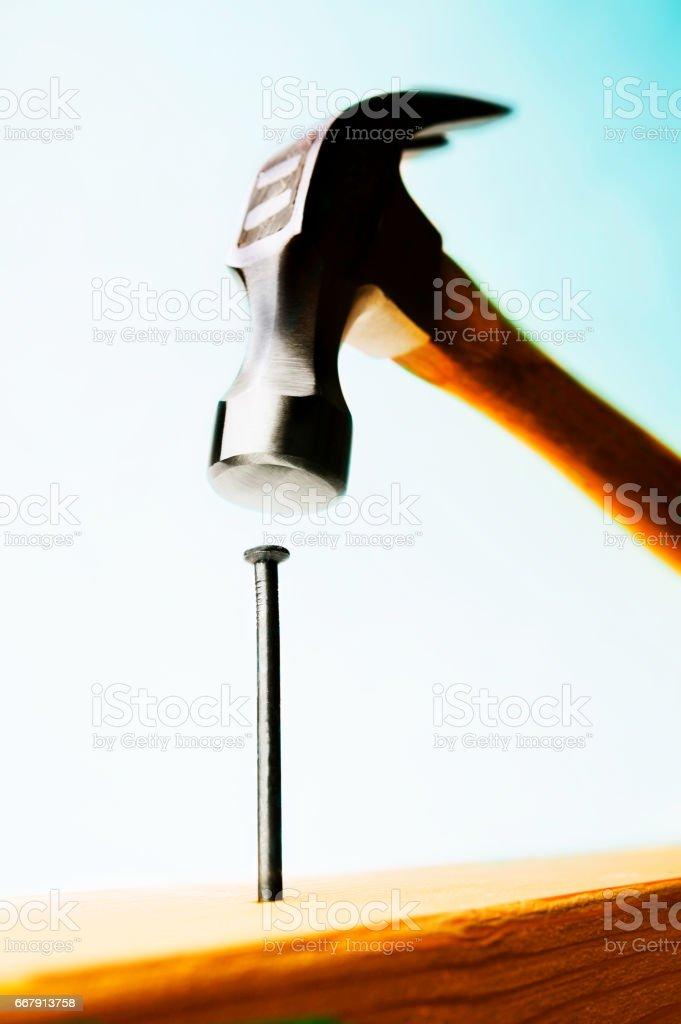 Hammer hitting nail. stock photo