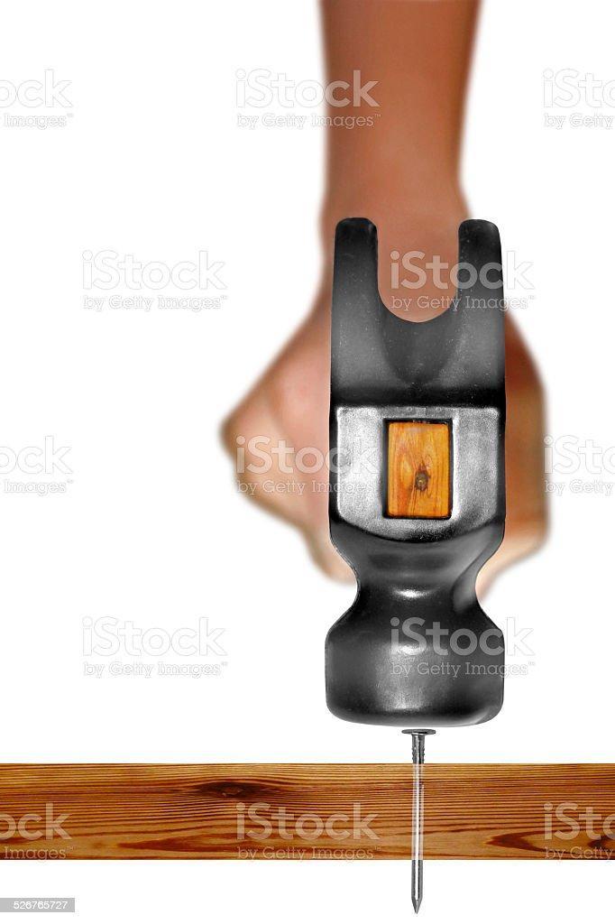 Hammer in Human Hand hitting a nail stock photo