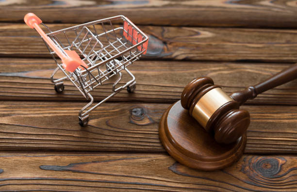 hammer of the judge, a trolley from a supermarket on a wooden background. stock photo