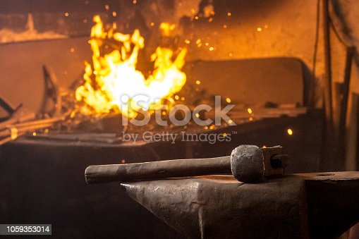 istock Hammer on anvil with fire of burning coal in background 1059353014