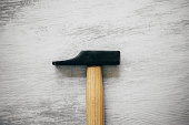 Hammer on wooden background. Construction and carpentry tools. Close up view of iron hammer with copy space. Top view.
