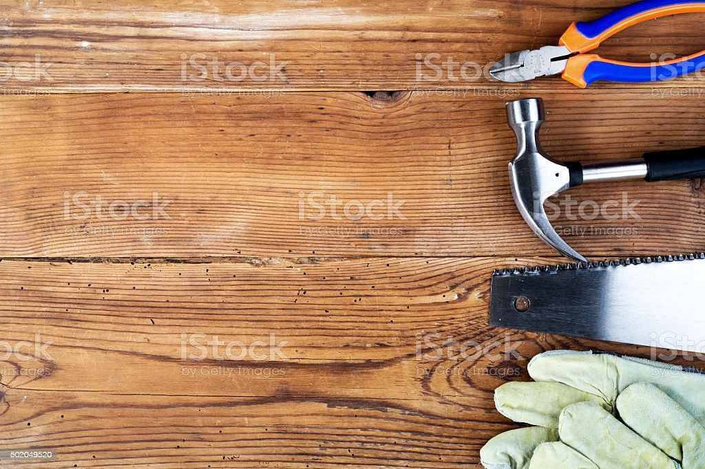 Hammer, protective gloves, pliers splitters and handsaw stock photo